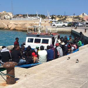 Ihmisiä laituriin kiinnitetyssä veneessä