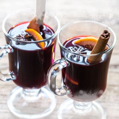 Pöydällä kaksi lasista, jalallista mukia. Mukissa glögiä. Koristeena appelsiinia, anista ja kanelintanko.