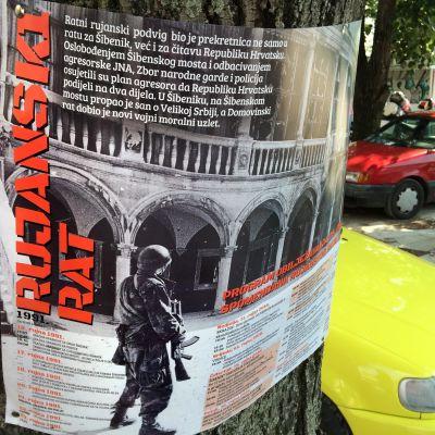 En kroatisk krigsaffisch som berättar om serbernas hemskheter mot kroaterna åren 1991-95. Affischen är fäst på ett träd.