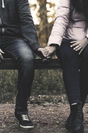 Ett par sitter hand i hand.