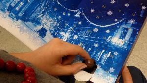 En hand plockar ut en chokladbit ur en adventskalender.