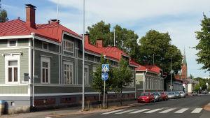 Vy längs Trädgårdsgatan i Åbo, med ett grönt trähus och Mikaelskyrkan i bakgrunden.