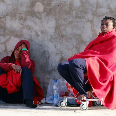 Kaksi punaisiin viltteihin kääriytynyttä naista.