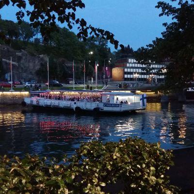 Fullt med människor ombord på restaurangfärjan Jakke jokilautta. Färjan lyser i rött och vitt i ån då han tar i land vid Teaterbron i Åbo en sommarnatt.