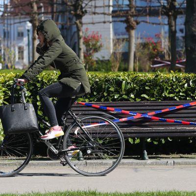 Nainen pyöräilee ohi penkin, jossa istumisen esteenä on eristysnauhaa.