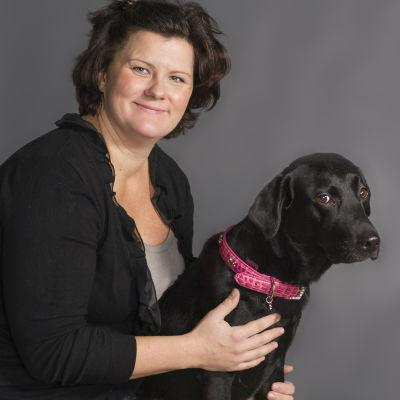 Veterinär Lotta Axelson som svarar på lyssnarnas frågor i Experttimmen, tillsammans med en svart labrador