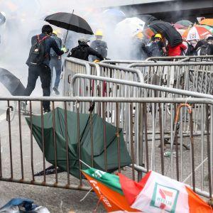 Demonstranter flyr polisens tårgas i Hongkong.