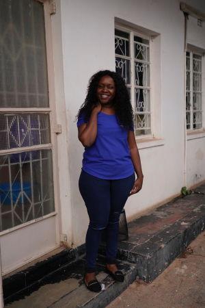 Florence står på trappan utanför ett hus. Hon var den som drog igång samtalsjouren 2003. Hennes största huvudvärk är att hitta finansiärer som kan garantera att verksamheten får fortsätta.