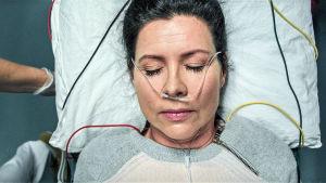 Nainen makaa sairaalasängyssä happiviiksissä silmät kiinni.