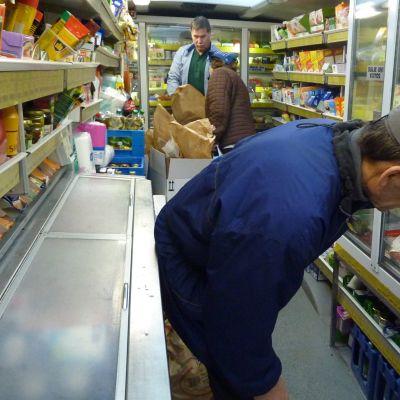Kauppa-autossa kauppis ja kaksi asiakasta.