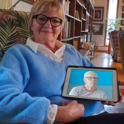 Nainen pitää kädessään tablettia, jolla näkyy hänen miehensä kuva.