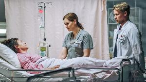 Nainen makaa sairaalasängyssä, hoitaja ja lääkäri vierellään.