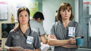 Sykkeen kaksi sairaanhoitajaa seisovat ja katsovat jotakin.