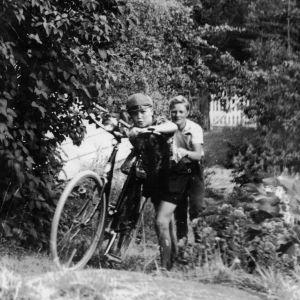 Kaksi poikaa kesäisessä maalaismaisemassa.