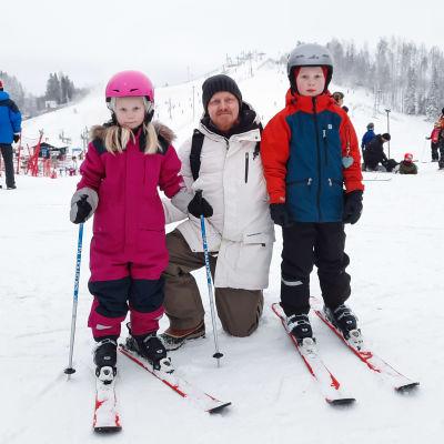 En man och två barn med slalomskidor poserar för kameran framför en slalombacke.