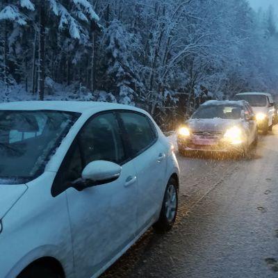 Autoja jonossa lumisella maantiellä