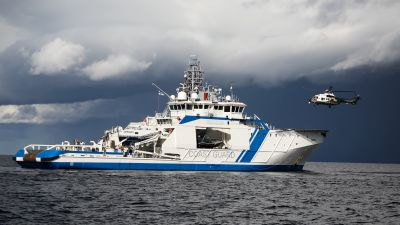 Räddningshelikopter landar på en patrullbåt ute till havs.