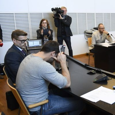 En häktad person döljer sitt ansikte framför kamerorna.