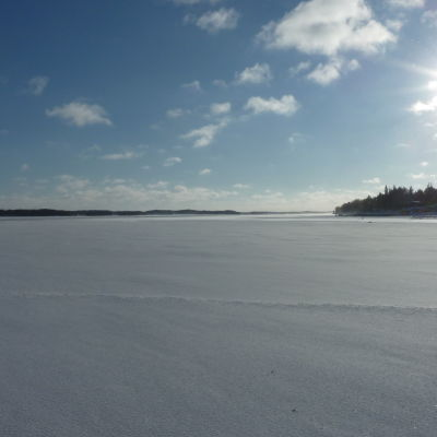 Solen skiner över isen på Skärgårdshavet en vinterdag.