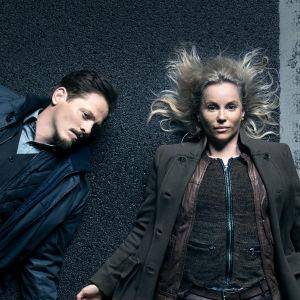 Karaktärerna Henrik och Saga ligger på en bro i mörkret.