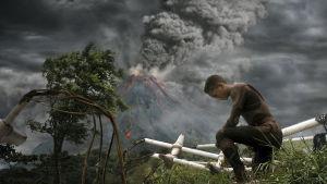 Barn som står på knä, vulkan i bakgrunden. Pressbild