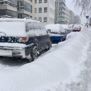 Parkerande bilar vid en oplogad trottoar.