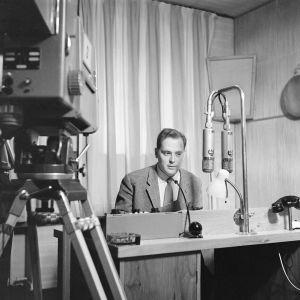 Toimittaja Paavo Noponen studiossa. Radion mikrofonit, mutta televisiokamera kuvaa.  (1959)