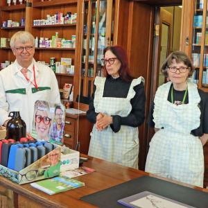 Farmaceuterna Bengt Mattila, Kristina Örnberg och Merja Rapeli bakom disken på Apotek Svanen.