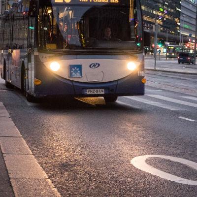 Bussi ajaa illan hämärtyessä.
