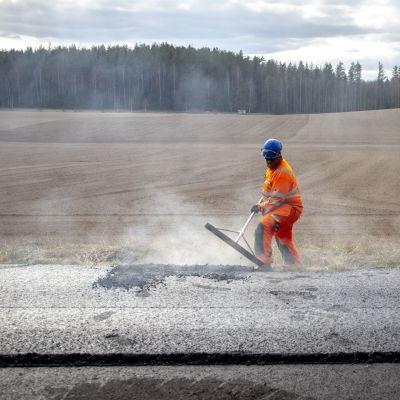 Mies tekee asfalttitöitä Lohjalla Koisjärven kylässä.