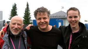 Saksofonistit Pentti Lahti ja Lenny Pickett sekä pasunisti Kasperi Sariola katsovat hymyillen kameraan.