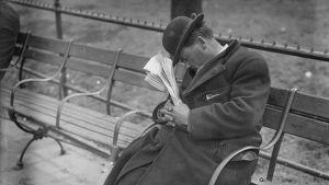 Mies nukkuu puistonpenkillä. Vanha kuva.