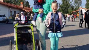 Ekaluokkalainen Alina äidin ja pikkusisaruksen kanssa Joroisten yhtenäiskoulun pihalla.
