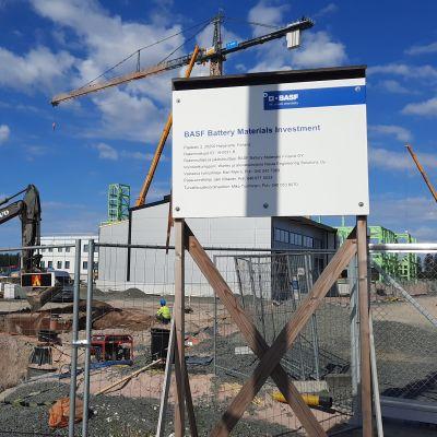 Tehtaan rakennustyömaalla kyltti, jossa kerrotaan, että BASF rakentaa paikalle akkumateriaalitehdasta.