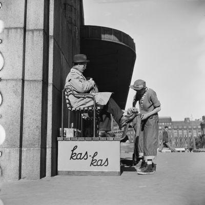 Poika lankkaa kenkiä rautatieaseman edessä 1950-luvulla.