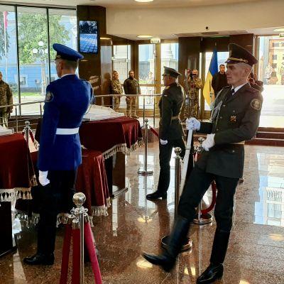 Soldater marscherar på ett tillbakalutat vis in i den lilla sal vid Ukrainas försvarsministerium där de i östra Ukraina stupades namn skrivs upp på en minnestavla och i en minnesbok.