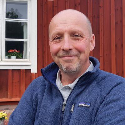 En glad man utan hår och med skägg i blå tröja står framför ett rött trähus med vita karmar och fönsterbågar.