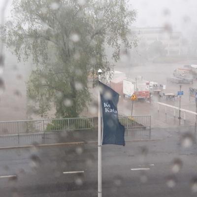 Näkymä ikkunasta sateiselle kadulle.
