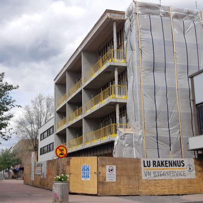 En ny byggnad byggs vid en gågata. Byggarbetsplatsen är omgärdad med höga staket.