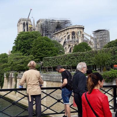 Turister på en bro framför den brandskadade katedralen Notre-Dame