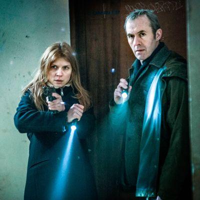 Mies ja nainen seisovat oven edessä pyssyt ja taskulamput käsissä.