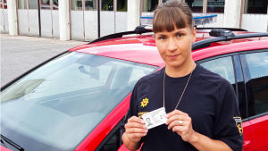 Palotarkastaja Anna Eskelinen pitää käsissään virkakorttiaan.