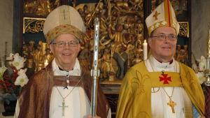 Biskop Gustav Björkstrand och ärkebiskop Jukka Paarma klädda i biskopsskrudar och med mitra och stav sida vid sida framför altaret i Pernå kyrka.