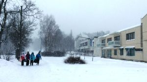 Barn går på en snöig gångled, kontors- och affärshus till höger, en stenkyrka skymtar i bakgrunden.