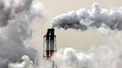 En fabriksskorsten spyr ut rök i en förort till Tokyo