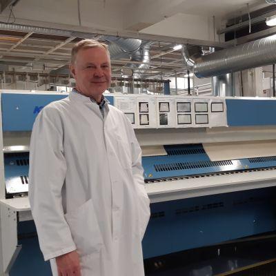 Mikkelin Pesulan toimitusjohtaja Kari Rämö seisoo suuren sairaalalakanoita mankeloivan koneen edessä.