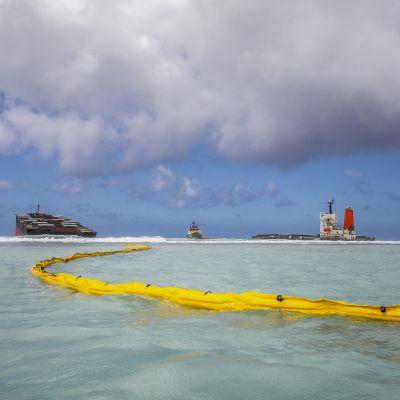 Öljypuomi meressä rahtilaivan edessä