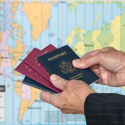 mies pitelee passeja käsissään, passi, usa, kartta