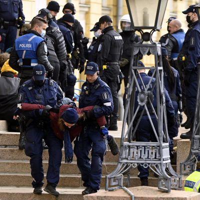 Poliisi kantoi mielenosoittajia bussiin yksi kerrallaan.