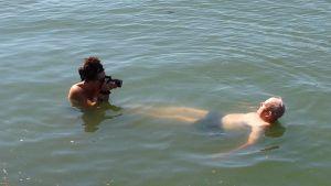 Meeri Koutaniemi valokuvaa meressä kelluvaa Caj Bremeriä. Kuva tv-dokumentin Caj Bremer, valokuvaaja kuvauksista.